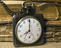 Retro pocket watch and tattered folios. Retro pocket watch on chain and tattered folios royalty free stock image