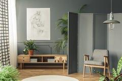 Retro poltrona contro uno schermo grigio accanto ad un disegno che appende o fotografia stock libera da diritti