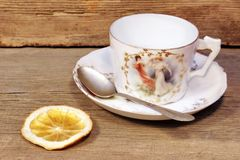 Retro  porcelain tea cup and plate with silver spoon Royalty Free Stock Image