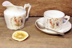Retro  porcelain tea cup and plate with silver spoon. In timber background, with space for text or image Royalty Free Stock Photos