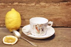 Retro  porcelain tea cup and plate with silver spoon. In timber background, with space for text or image Stock Photo