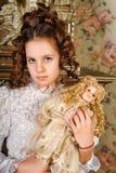 Retro- Porträt eines Mädchens mit einer Porzellanpuppe Stockfoto