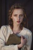 Retro- Porträt eines schönen träumerischen Mädchens, das draußen ein Buch in den Händen hält Weiches Weinlesetonen Lizenzfreies Stockbild