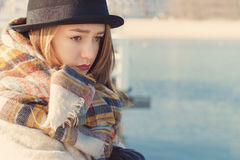 Retro portrait beautiful young sad girl in hat and coat stands on the dock Stock Photos