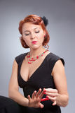 Retro portrait of pretty woman with red manicure Stock Image