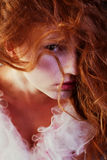 Retro portrait of red-haired queen like girl. In white dress. Perfect glossy long hair. Wild glance. Close up. Vintage style. Arty make-up. Studio shot Royalty Free Stock Images