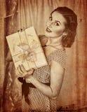 Retro portrait of woman keeps gift box. Retro portrait of woman holding gift box. Black and white retro on old paper Royalty Free Stock Image