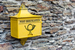 A retro postbox in yellow color in Marksburg, Germany. Royalty Free Stock Photos