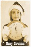 Retro postcard with girl in santa claus hat and clock. Close up Royalty Free Stock Photography