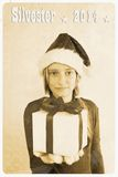 Retro postcard - girl in santa claus hat giving gift. Vertical Royalty Free Stock Image