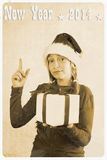 Retro postcard - girl in santa claus hat and show sign. Vertical Stock Image