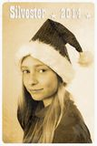 Retro postcard with girl in santa claus hat. Vertical Royalty Free Stock Photography