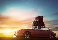 Retro röd bil med bagage på takkuggen på solnedgången Lopp semesterbegrepp Arkivfoto