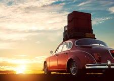 Retro röd bil med bagage på takkuggen på solnedgången Lopp semesterbegrepp Arkivbilder