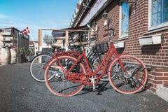 Retro röd cykel på gatan nära kafét arkivbild