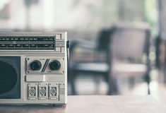 Retro radio cassette stereo on wooden table. In vintage color tone Royalty Free Stock Photos