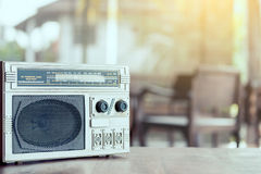 Retro radio cassette stereo on wooden table. In vintage color tone Royalty Free Stock Image