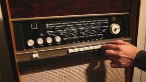 Retro radio, de man verandert de frequentie op de oude radioontvanger, de frequentieverandering op de oude ontvanger stock videobeelden