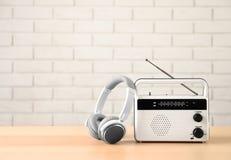 Retro radio och hörlurar på tabellen mot väggen Fotografering för Bildbyråer