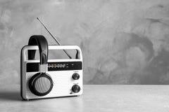 Retro radio och hörlurar på tabellen mot väggen Royaltyfri Bild