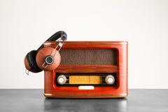 Retro radio och hörlurar på tabellen mot väggen Royaltyfri Foto