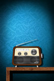Retro radio on wood table with blue wallpaper Stock Photo