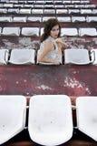 Retro ragazza che si siede nello stadio Immagini Stock Libere da Diritti