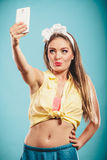 Retro ragazza con lo smartphone che prende selfie Immagini Stock
