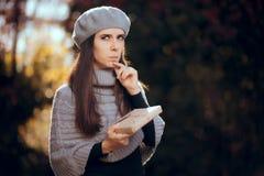 Retro ragazza elegante con il berretto che tiene un pacchetto imballato con carte fotografia stock