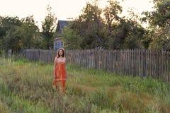 Retro ragazza sola spaventata nella campagna che cammina lungo l'alta erba nella sera lungo le costruzioni abbandonate del villag fotografie stock