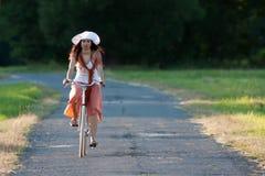 Retro ragazza sulla vecchia bici immagine stock