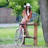 Retro ragazza sulla vecchia bici immagini stock