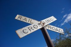 Retro railroad crossing sign. Old retro railroad crossing sign with blue sky in background royalty free stock image