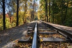 Retro railroad passes through a picturesque autumn forest. Оld railroad and small bridge passes through a picturesque autumn city forest on sunny day, view stock images