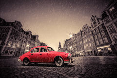 Retro red car on cobblestone historic old town in rain. Wroclaw, Poland. Retro red car on cobblestone historic old town in rain. The market square at night royalty free stock photography