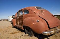 Retro Red Car in Junkyard. Old retro red vehicle in a desert junkyard stock image