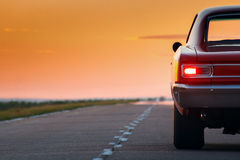 Retro red car standing on asphalt road at sunset stock photography