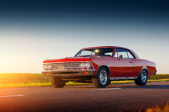 Retro red car stay on asphalt road at sunset Royalty Free Stock Image