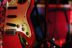 Retro Red Guitar. Retro style red guitar caught in shaft of white stage lighting Stock Photo