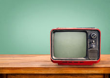 Retro red television on wood table. With vintage aquamarine wall background Royalty Free Stock Image