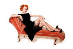 Beautiful retro redhead on chaise longue Stock Photos