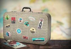 Retro resväska med stikkers på golvet Arkivbild