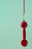 Retro ricevitore telefonico rosso che appende dal cavo a spirale su Aqua Back fotografia stock libera da diritti