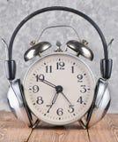 Retro ringklocka med hörlurar på trätabellen på grå betongväggbakgrund fotografering för bildbyråer