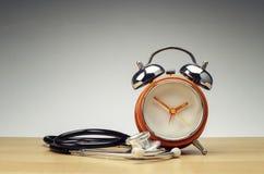 Retro ringklocka och stetoskop på träskrivbordet över lutningeffektbakgrund royaltyfri fotografi