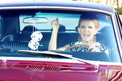 Retro Road Rage. Angry red head woman with sixties makeup and wardrobe driving in retro muscle car waving fist Stock Photo