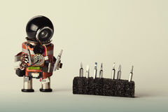 Retro robot with screwdriver set. Fun toy repair man character, black helmet head and hardware instrument. Macro view, shallow stock image