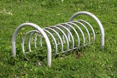 Retro rocznik stronniczo rdzewiał popielatego metalu bicyklu stojaka otaczającego z uncut trawą w lokalnym jawnym parku obraz stock