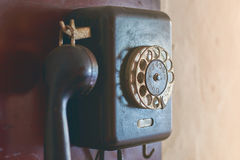 Retro rotary dial phone hanging on the wall Stock Photos