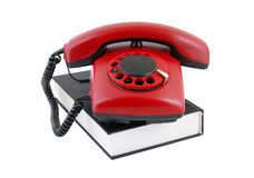 Retro rotary telephone on black book Stock Photo